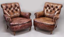 A SUPERB PAIR OF DEEP LEATHER ARMCHAIRS with curving buttoned back, on turned legs with castors.