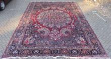 A GOOD LARGE MESHED CARPET, claret ground with all-over stylised floral decoration, signed. <br>18ft 3ins x 11ft 7ins.