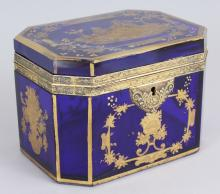 A LOVELY 19TH CENTURY BLUE GLASS BOX AND COVER, POSSIBLY FRENCH, with gilded decoration, lovers in a garden setting, flowers and motifs.  6ins long.