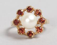A GOLD, GARNET AND PEARL RING.