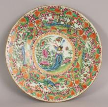 A 19TH CENTURY CHINESE CANTON PORCELAIN DISH, painted with squirrel bordered panels of birds in garden settings, 9.1in diameter.