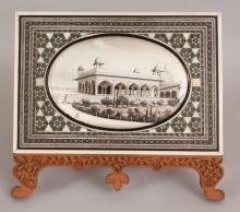 A GOOD 19TH/20TH CENTURY FRAMED INDIAN PAINTING ON IVORY OF A PALACE, rendered in black and gilding, within a mosaic onlaid sandalwood display frame, the frame 8.1in wide x 7.3in high.