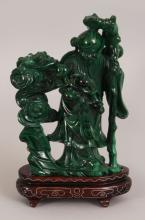 AN EARLY 20TH CENTURY CHINESE MALACHITE CARVING OF SHOU LAO, together with a fitted silver-wire inlaid wood stand, the deity bearing a frond of peach, 5.9in high, the stone itself 3.7in wide at widest point & 5in high.