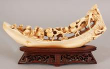 AN EARLY 20TH CENTURY CHINESE CARVED IVORY MODEL OF A RIVER BOAT, together with a fitted carved and pierced wood stand, the boat formed from a trunk of pine and carrying a sage and his boy attendant in the company of a frog, 4.75in high, the ivory itself 7.8in long & 3.5in high.