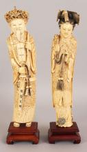 A GOOD PAIR OF EARLY 20TH CENTURY CHINESE IVORY CARVINGS OF AN EMPEROR & AN EMPRESS, together with fixed wood stands, the emperor in dragon robes, the empress in phoenix robes, each with black stained hair and tassels, 14in & 13.5in high overall.