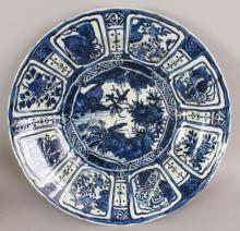 A GOOD LARGE CHINESE WANLI PERIOD MING DYNASTY KRAAK BLUE & WHITE PORCELAIN CHARGER, painted to the centre with a cricket perched on rockwork in a river landscape setting, within a border of floral and emblem lappet panels, 19.1in diameter.