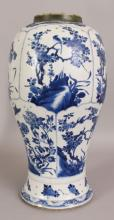 A LARGE CHINESE KANGXI PERIOD BLUE & WHITE PORCELAIN VASE, the sides painted in a vivid tone of underglaze-blue with a variety of shaped panels of foliage and rockwork, 16.7in high.