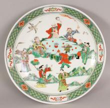 A GOOD QUALITY EARLY 20TH CENTURY CHINESE FAMILLE VERTE PORCELAIN DISH, of saucer shape, painted with seven Immortals and a boy attendant in a rocky landscape setting with a stork in flight overhead, the base with an artemisia leaf in iron-red, 13.3in diameter.