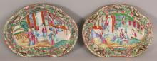 A GOOD PAIR OF 19TH CENTURY CHINESE CANTON MANDARIN RUYI DISHES, each painted in vivid enamels and gilding with a figural terrace scene within an elaborate floral, bird and lantern panel border, 11.in wide x 8.4in at widest points.