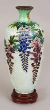 A SIGNED JAPANESE MEIJI PERIOD CLOISONNE GIN BARI VASE, together with a fitted wood stand, the vase decorated with hanging wisteria, the base with an impressed mark, the vase itself 5.8in high.