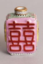 A CHINESE FAMILLE ROSE MOULDED PORCELAIN SNUFF BOTTLE, each side decorated with a double heaven Shuangxi auspicious character, 2in high.