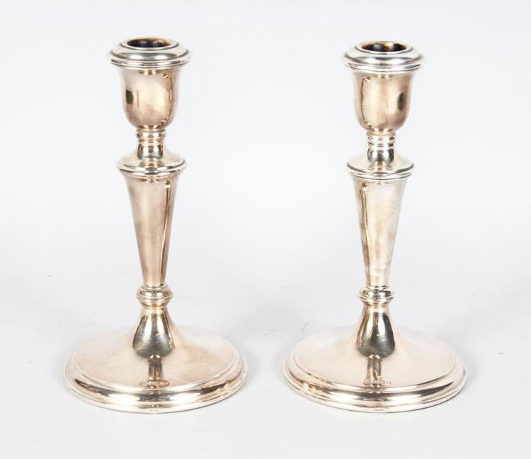 A PAIR OF PLAIN CIRCULAR CANDLESTICKS with loaded bases. 8ins high, London 1977.