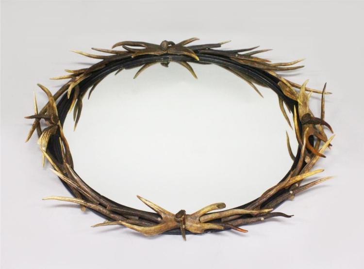 A LARGE ANTLER OVAL MIRROR, the frame entwined with antlers of various sizes. 4ft 6ins high x 3ft 2ins wide (Provenance: Anthony Redmile).