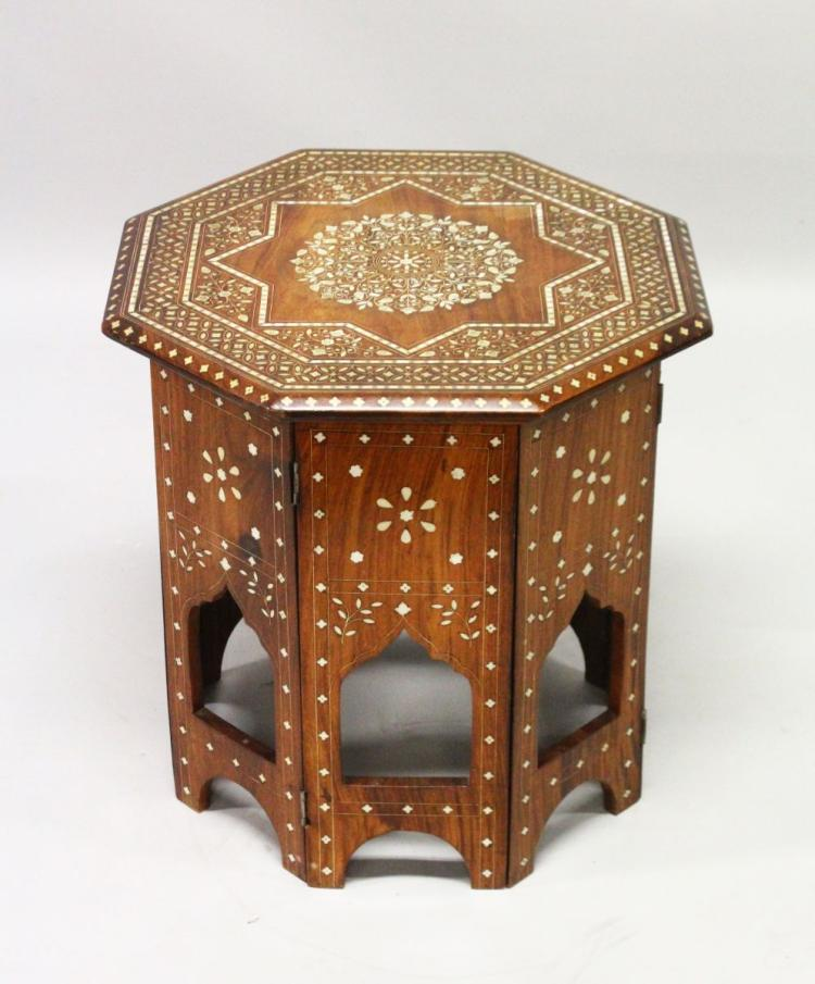 AN INDIAN OCTAGONAL SHAPED FOLDING TABLE, CIRCA 1900, with profusely inlaid floral decoration. 1ft 8ins high x 1ft 8ins wide.