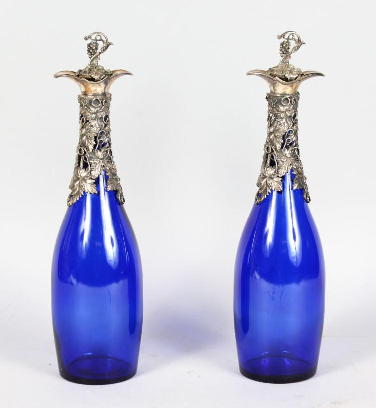 A PAIR OF BRISTOL BLUE BOTTLES, with plated cast mounts and stoppers. 13.5ins high.