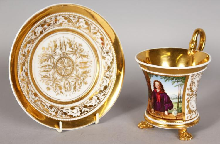 A LOVELY BERLIN CUP AND SAUCER, white and gilt, painted with an oval of a girl holding a bird and supported on claw feet.