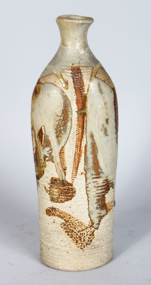A STUDIO POTTERY VASE, CIRCA. 1960'S, of cylindrical freeform design with slip glaze decoration. 10.5ins high.
