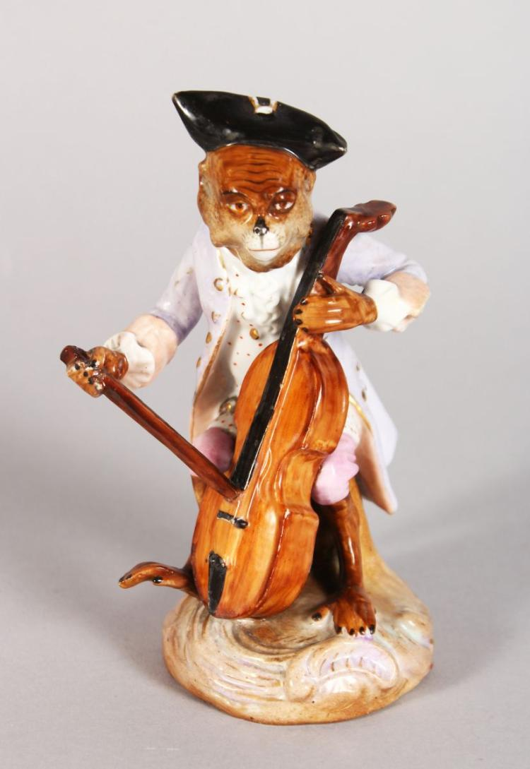 A CONTINENTAL PORCELAIN MONKEY FIGURE PLAYING A CELLO. 5in high.