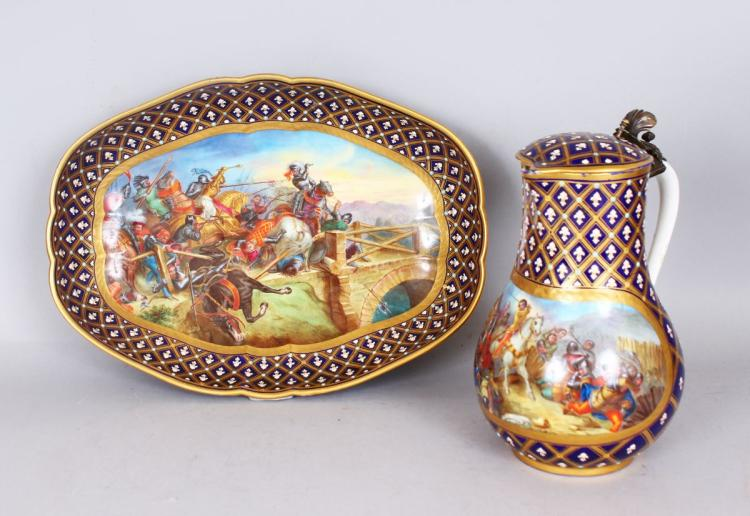 A SUPERB PAIR OF 18TH CENTURY SEVRES JUG AND BASIN, painted with battle scenes, dated 1503, the jug with blue and white fleur-de-lys and cross gilt pattern, a painted battle scene, 7ins high, and A MATCHING BASIN, 11.5ins (2).