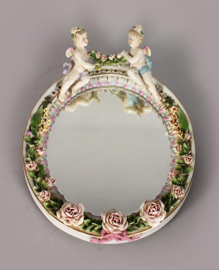 A MEISSEN STYLE PORCELAIN MIRROR, with a pair of cherubs and floral encrusted frame. 12ins high.