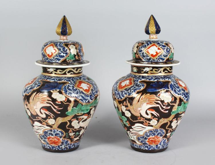 A PAIR OF JAPANESE IMARI STYLE VASES AND COVERS, decorated with cranes, flowers and trees. 1ft 3ins high.