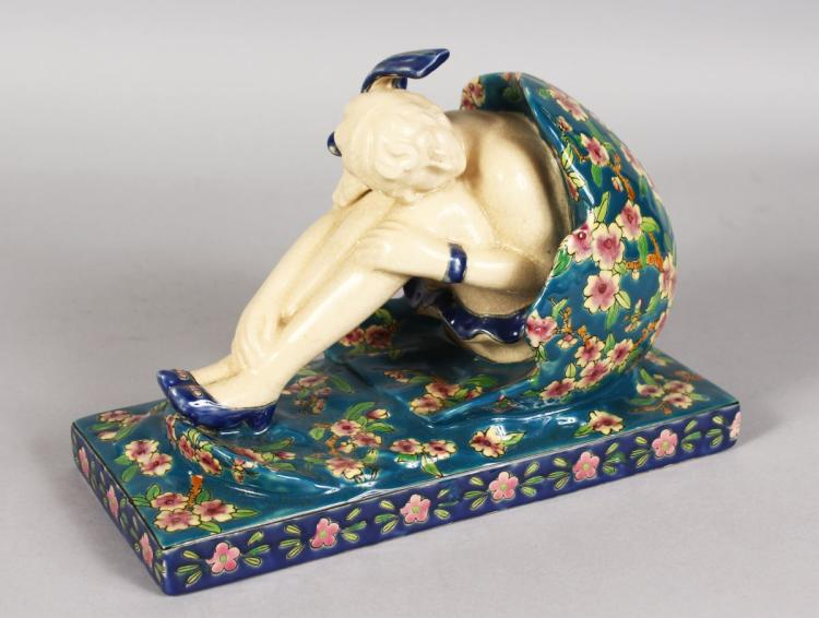 A FRENCH POTTERY GROUP, woman on an egg. 10ins long.