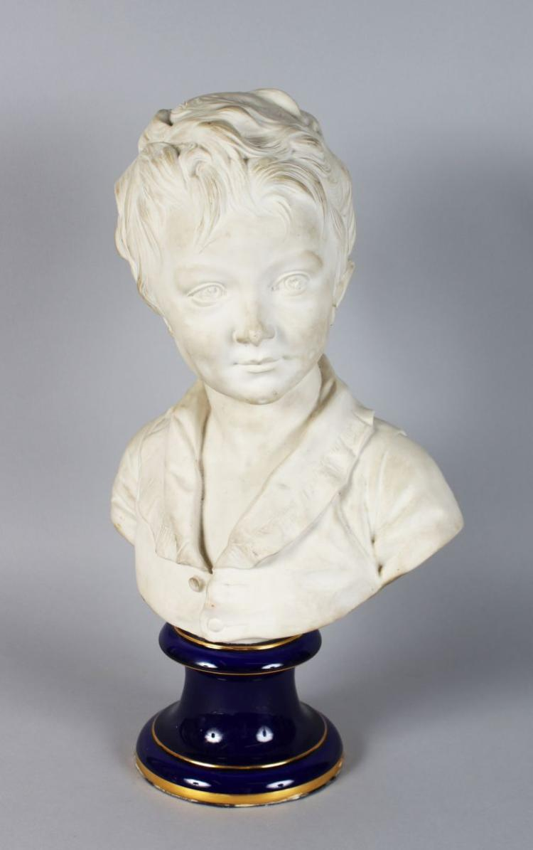 AFTER HOUDON. A WHITE PORCELAIN BUST OF A YOUNG BOY, Signed Houdon, on a blue base. 13ins high.