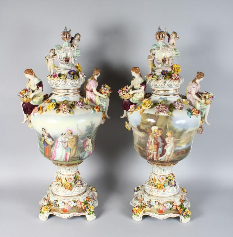 A SUPERB PAIR OF MEISSEN DESIGN FLOWER ENCRUSTED URNS, COVER AND STANDS, the bodies painted with scenes of classical figures and flowers with female handles carrying baskets of flowers. 34ins high.