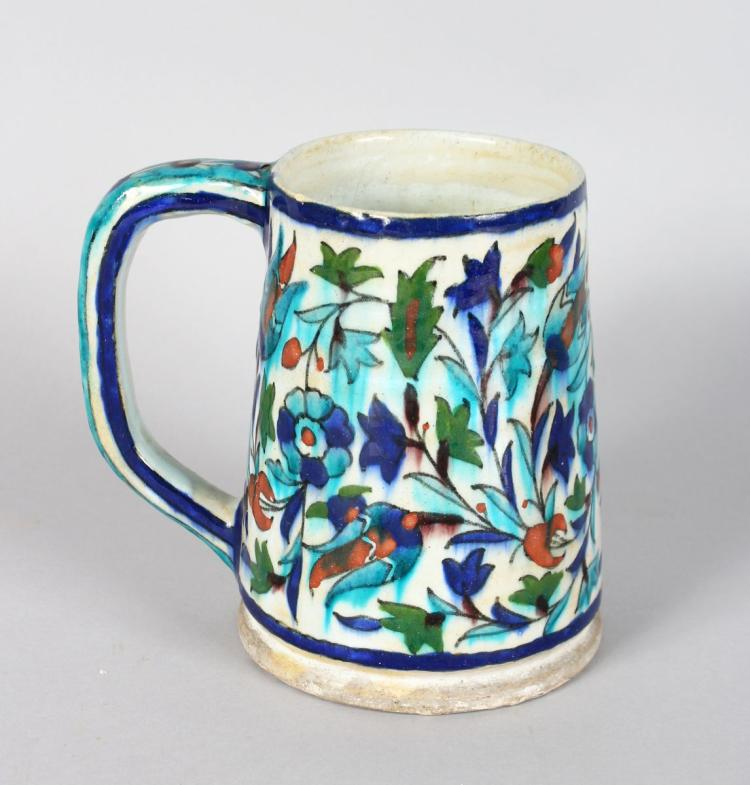 AN IZNIK POTTERY TANKARD with leaves and flowers in red and blue. 6ins high.