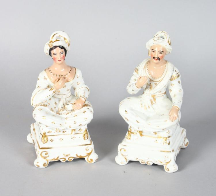 A PAIR OF SEATED FIGURES OF A TURKISH MAN AND WOMAN sitting cross legged on stools. 6ins high.
