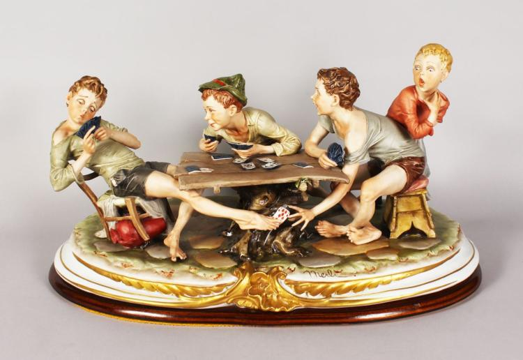 A SUPERB LARGE CAPODIMONTE PORCELAIN GROUP, four boys playing and cheating at cards, around a rustic table. Signed MERLI. Mark in blue. 21ins long x 11.5ins high.