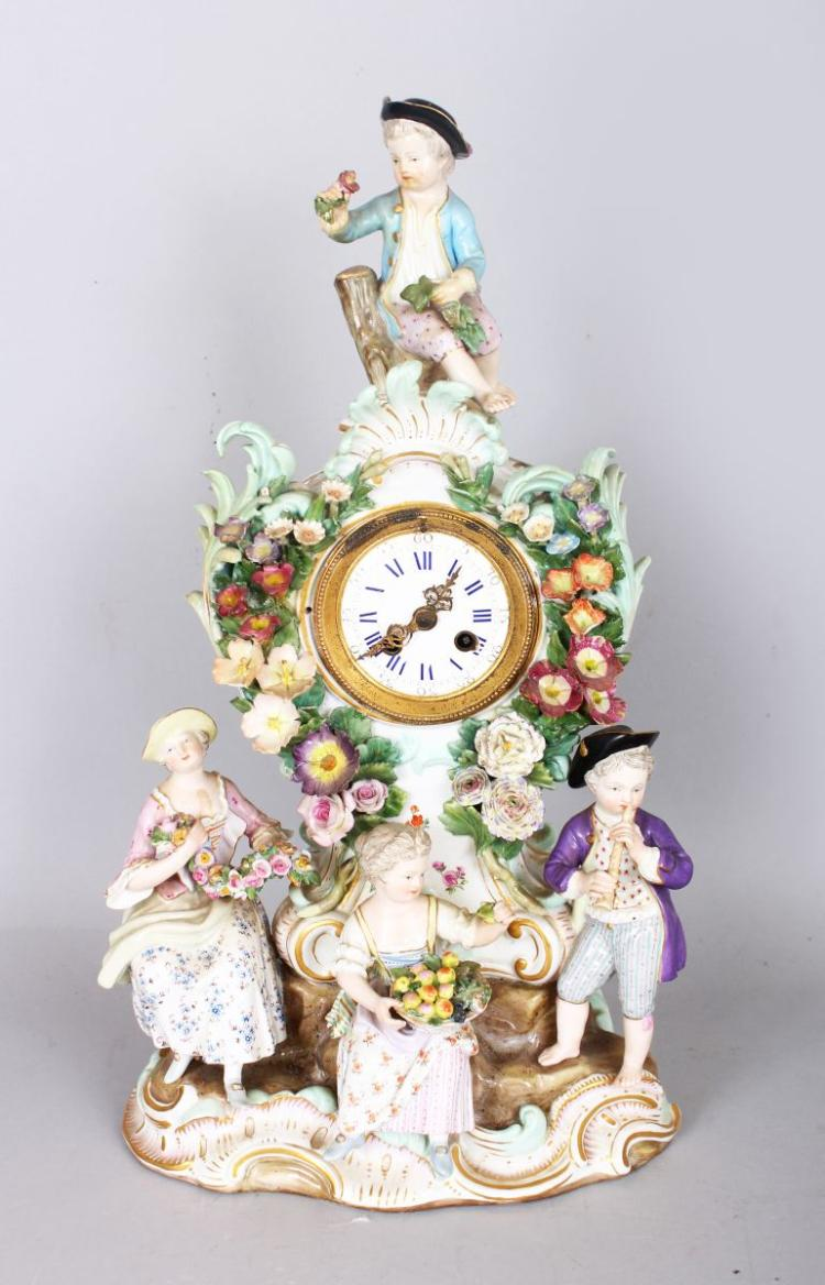 A VERY GOOD 19TH CENTURY MEISSEN PORCELAIN CLOCK, with drum movement by HENRY MARC, PARIS, with white enamel dial, blue and white Roman numerals, the case with four figures carrying baskets of fruit, garlands and musical instruments, also scrolls and encrusted with flowers. Cross swords mark in blue. 14ins high.