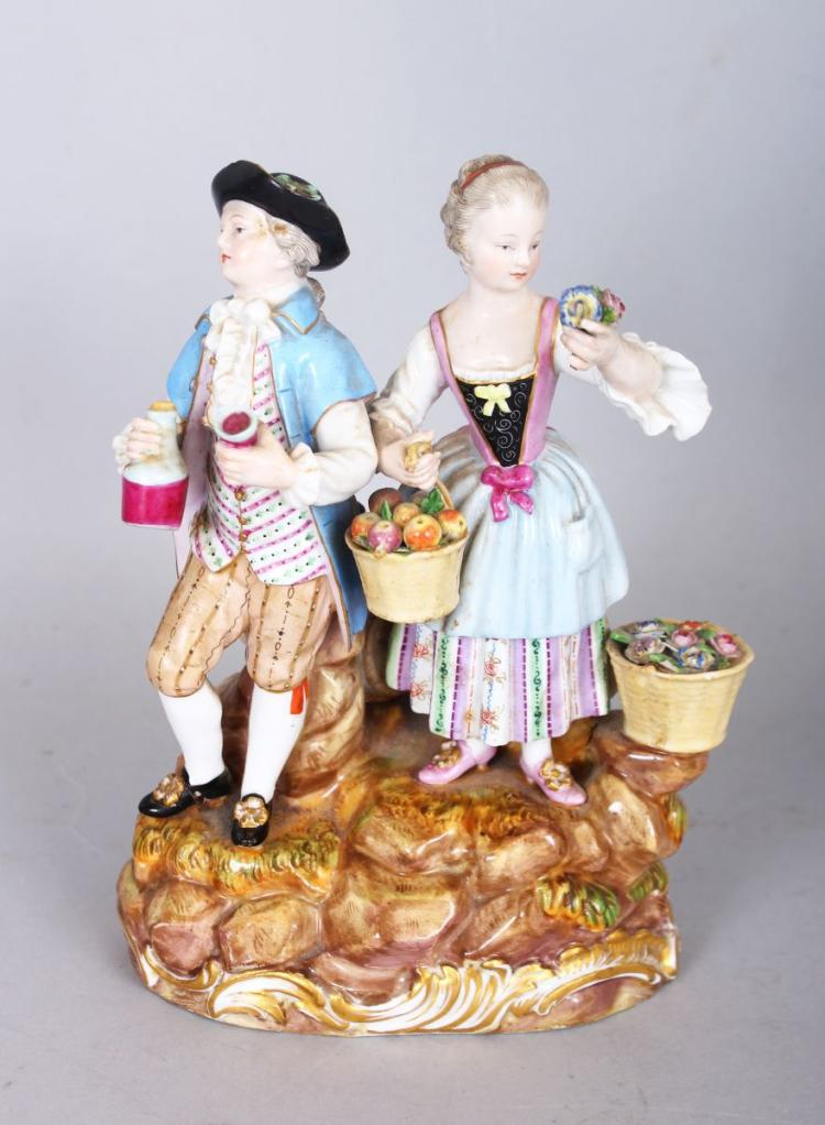 A GOOD 19TH CENTURY MEISSEN GROUP OF A GALLANT AND LADY carrying a jug, basket of fruit and posy, standing on a rocky base. Cross swords mark in blue. 6.5ins high.