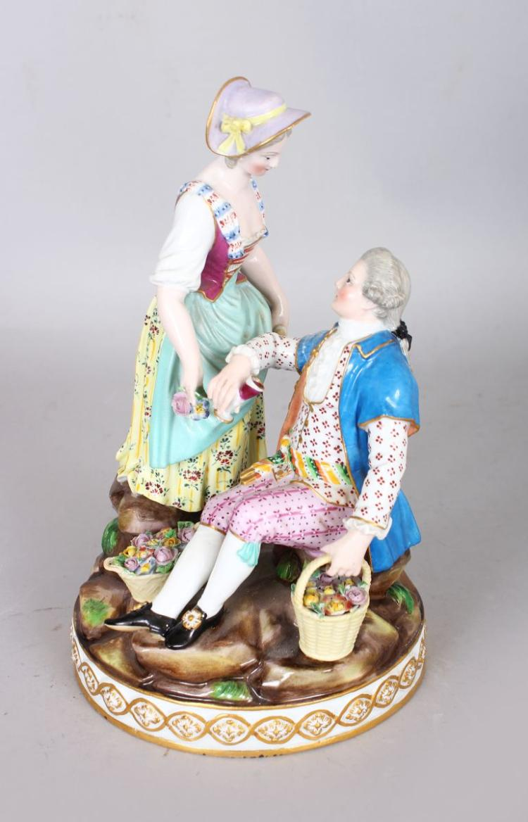 A 19TH CENTURY MEISSEN GROUP OF A SEATED GALLANT AND LADY, she is standing by his side on a circular base. Cross swords mark in blue. 7.5ins high.