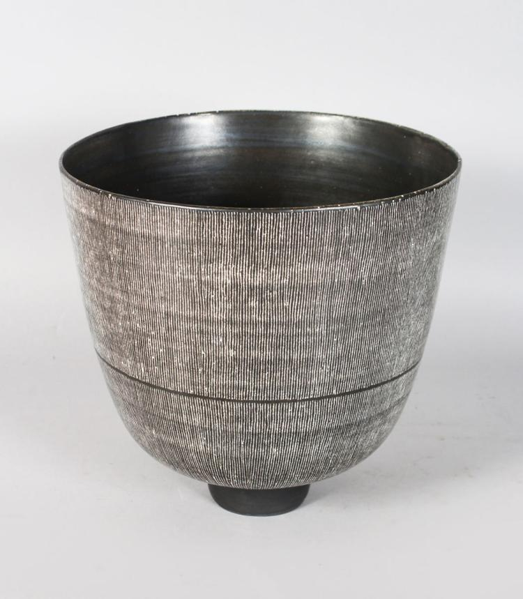 A GOOD LARGE CIRCULAR BOWL by RUPERT SPIRA, of slightly tapering form, dark grey matt glaze with fine white vertical striped decoration, on a small footed base, raised RS mark. 9ins high.