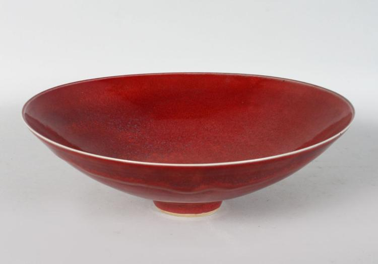 A GOOD CIRCULAR BOWL by RUPERT SPIRA, of broad conical form, with a flambe glaze, on a small footed base, raised RS mark. 12ins diameter.