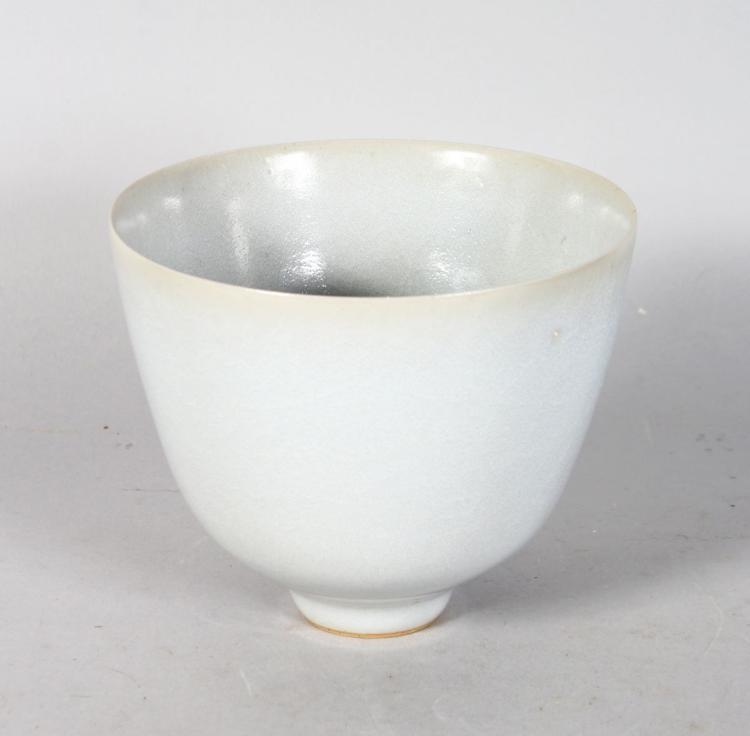 A CIRCULAR BOWL OR VASE by RUPERT SPIRA, of tapering form, with a pale grey glaze, on a footed base, raised RS mark. 5.5ins high.