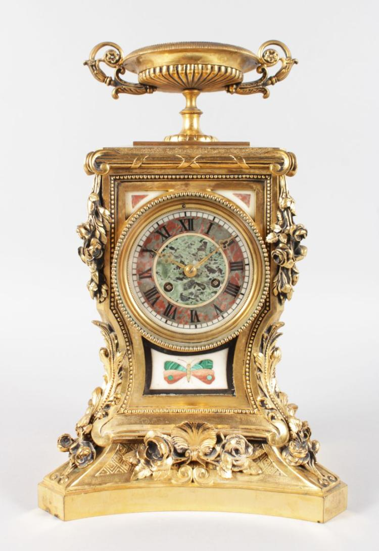 A SUPERB LOUIS XVI ORMOLU AND PIETRA DURA MANTLE CLOCK, with eight-day movement striking on a single bell, with urn finial, acanthus and roses, the dial and panels with inlaid Pietra Dura, one with a butterfly. 14ins high.