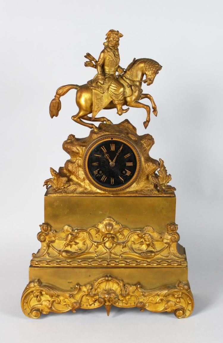 A 19TH CENTURYFRENCH GILT MANTLE CLOCK with enamel dial, eight day movement, surmounted by a man on a horse. 19ins high.
