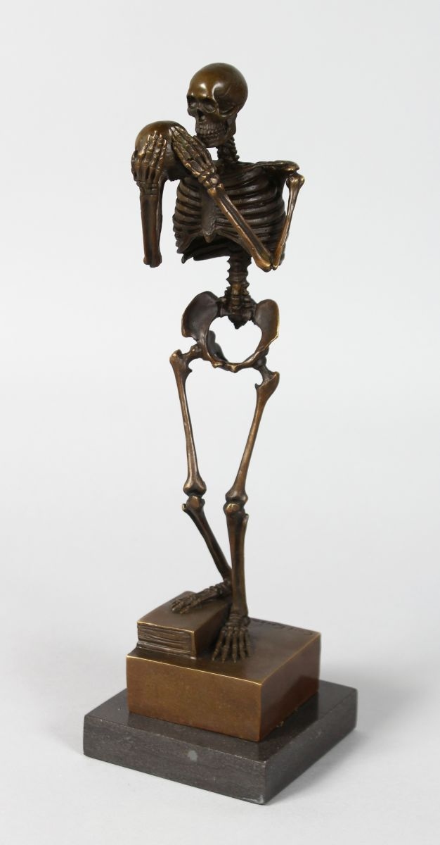 AFTER CARL KAUBA (1865-1922) AUSTRIAN A BRONZE STANDING SKELETON holding a skull. Signed, 12ins high, on a marble base.
