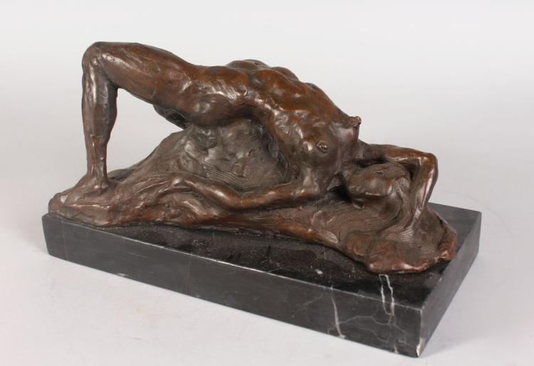 AN ABSTRACT BRONZE FEMALE NUDE, reclining on a rock, on a rectangular marble base. 1ft 1ins long.