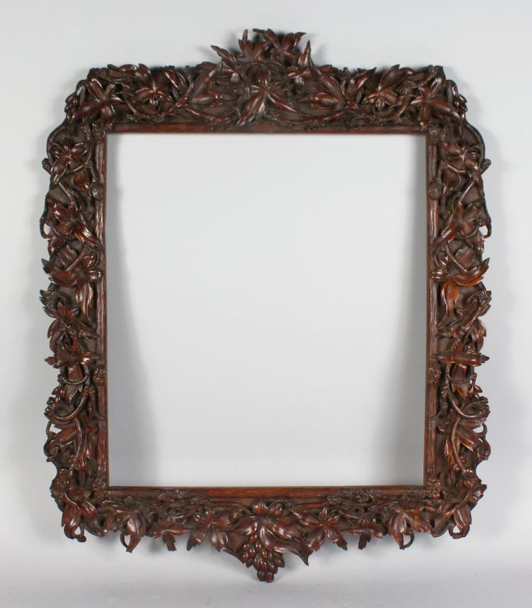 A WELL CARVED WALNUT FOLIAGE PICTURE FRAME. 28ins long x 23ins wide.