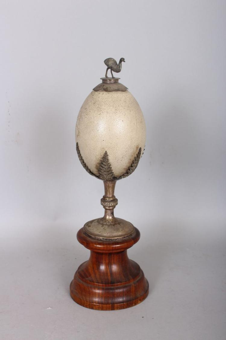 AN AUSTRALIAN MOUNTED EMU EGG, on a plated stand with small emu on the top. 9ins high including stand.