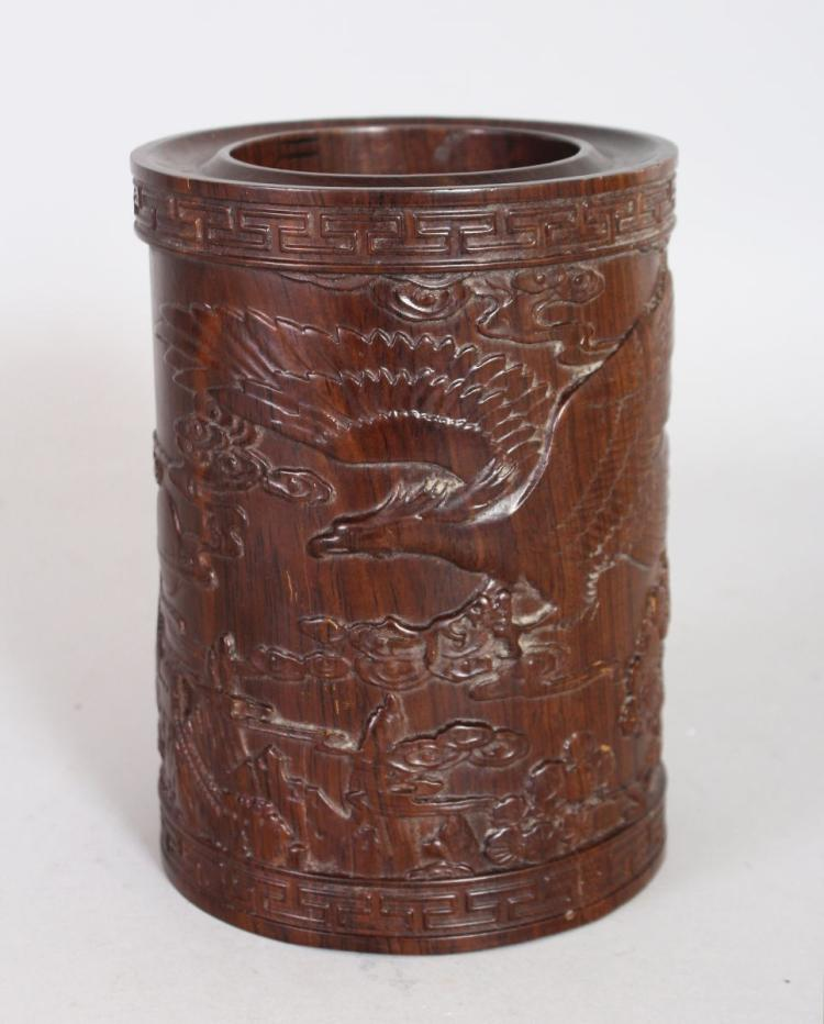 A CHINESE CARVED ROSEWOOD BRUSHPOT, carved with an eagle on a mountainous landscape. 6ins high.