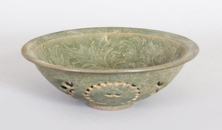A CHINESE GREEN CELADON POTTERY BOWL, with pierced decoration. 7ins diameter.