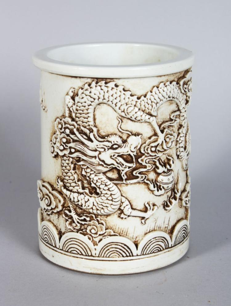 A CHINESE BLANC DE CHINE BRUSH POT, relief decorated with dragons. 5.5ins high.