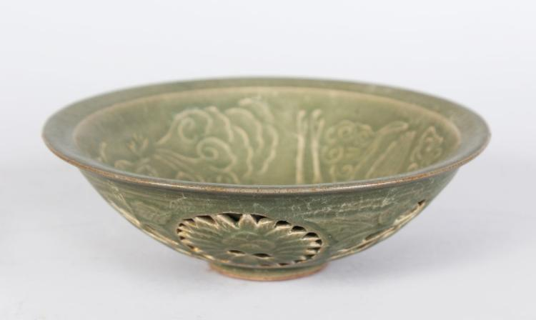 A CHINESE CELLADON BOWL, with incised and pierced decoration. 7ins diameter.