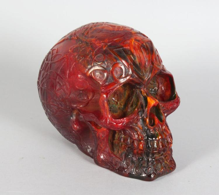 AN UNUSUAL AMBER STYLE MODEL OF A HUMAN SKULL. 6ins long.