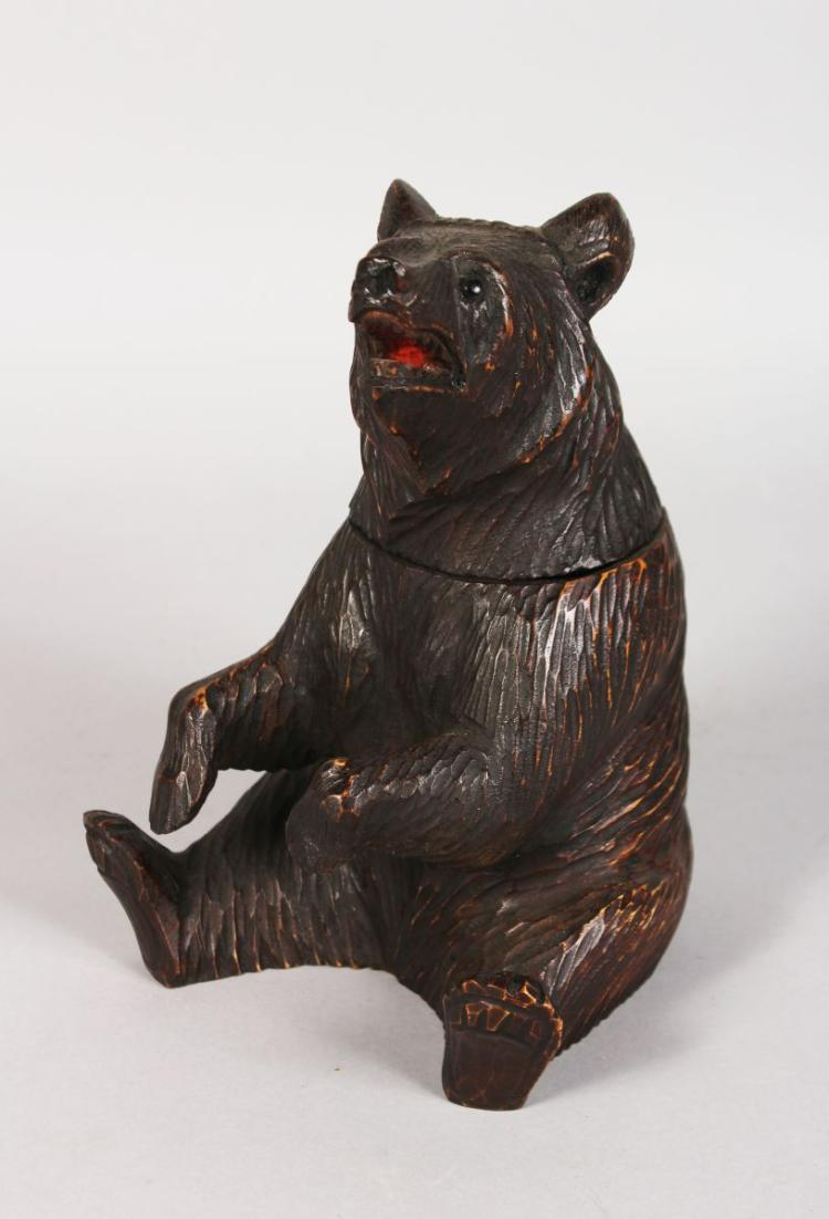 A BLACK FOREST CARVED WOOD SEATED BEAR TOBACCO JAR with hinged head and glass eyes. 8ins high.