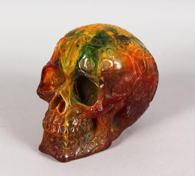 AN AMBER TYPE CARVED SKULL. 6.5ins.